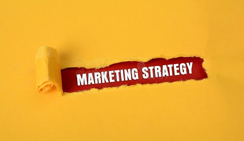 Diseño de estrategia de marketing en papel amarillo rasgado imágenes de archivo libres de regalías