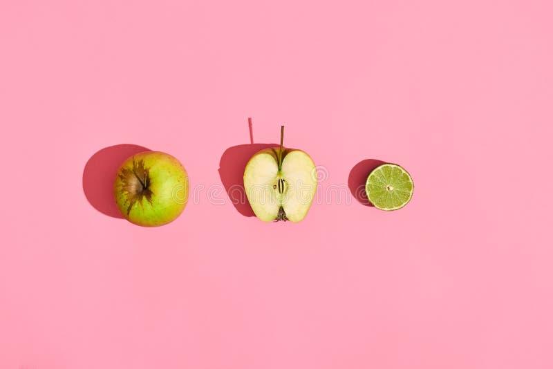 Diseño de la comida Composición de frutas frescas, de la manzana verde, de la mitad de la manzana verde y de la cal en fondo cora fotografía de archivo libre de regalías