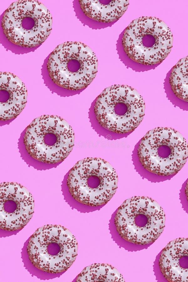 Diseño de la comida con el buñuelo esmaltado rosado sabroso en modelo en colores pastel de la opinión de top del fondo de la lila foto de archivo libre de regalías