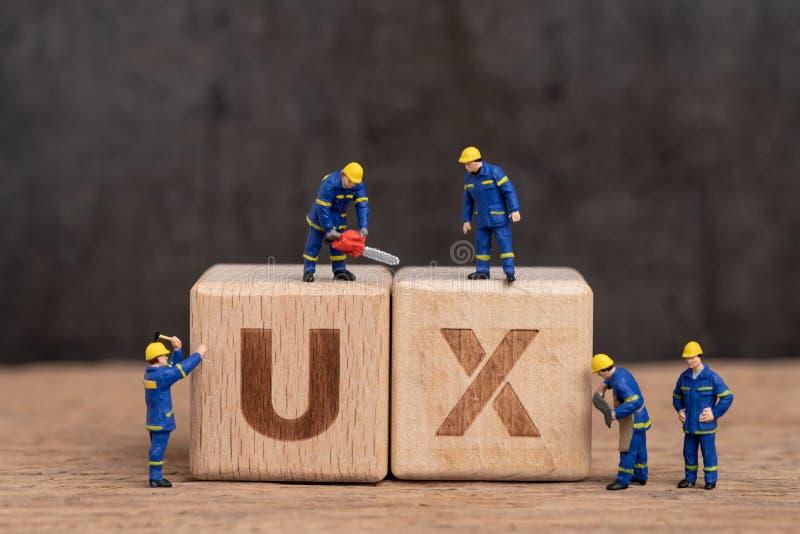 Diseño de la experiencia del usuario en producto y concepto del servicio, trabajadores miniatura de la gente con el bloque de mad fotografía de archivo libre de regalías