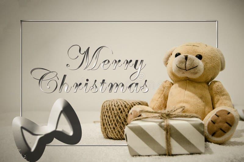 Diseño de la postal de la Feliz Navidad con el oso de peluche y la caja de regalo fotografía de archivo libre de regalías