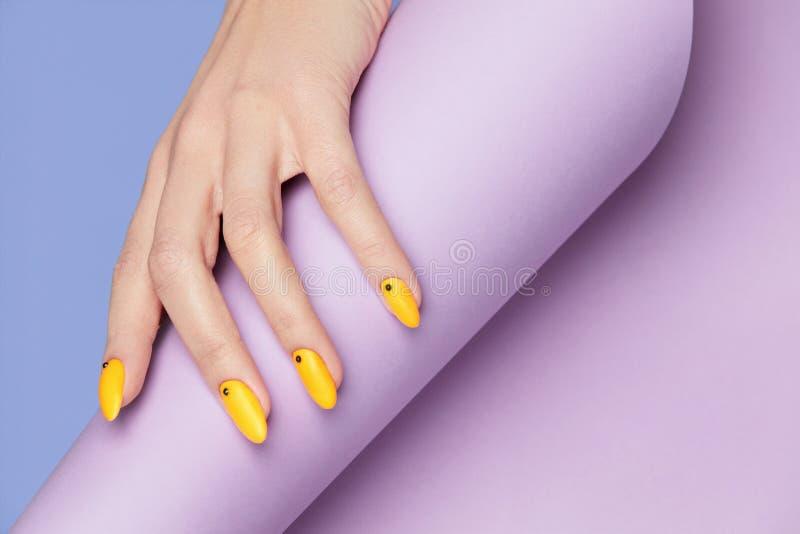 Diseño de los clavos Manos con la manicura amarilla brillante fotos de archivo