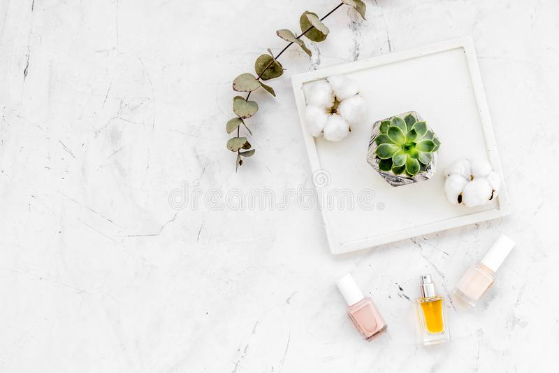 Diseño del escritorio del trabajo con las decoraciones, el esmalte de uñas y el perfume concretos en la maqueta de mármol blanca  imagenes de archivo
