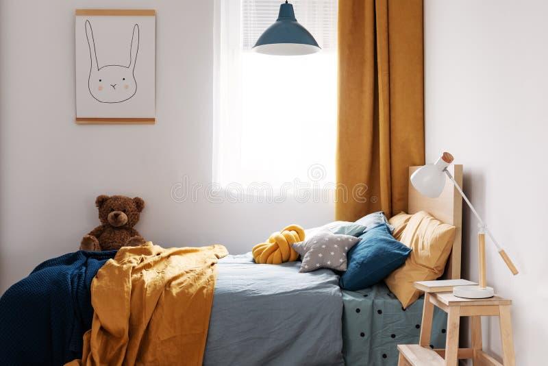 Diseño elegante del dormitorio del niño azul y anaranjado en el apartamento brillante imagenes de archivo
