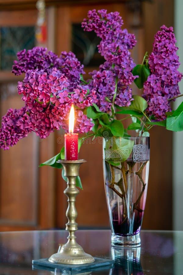 Diseño interior con una vela roja ardiente y un florero imagenes de archivo