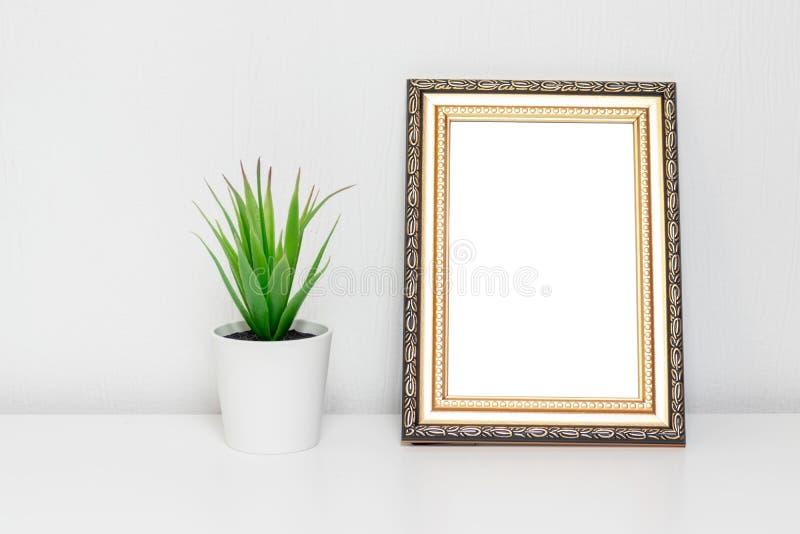 Diseño interior de Minimalistic con el marco de la foto y una planta en el pote blanco en un escritorio imágenes de archivo libres de regalías