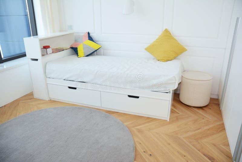 Diseño interior del dormitorio moderno con la cama blanca de lujo del niño, diseño interior contemporáneo y alfombra acogedora imagenes de archivo