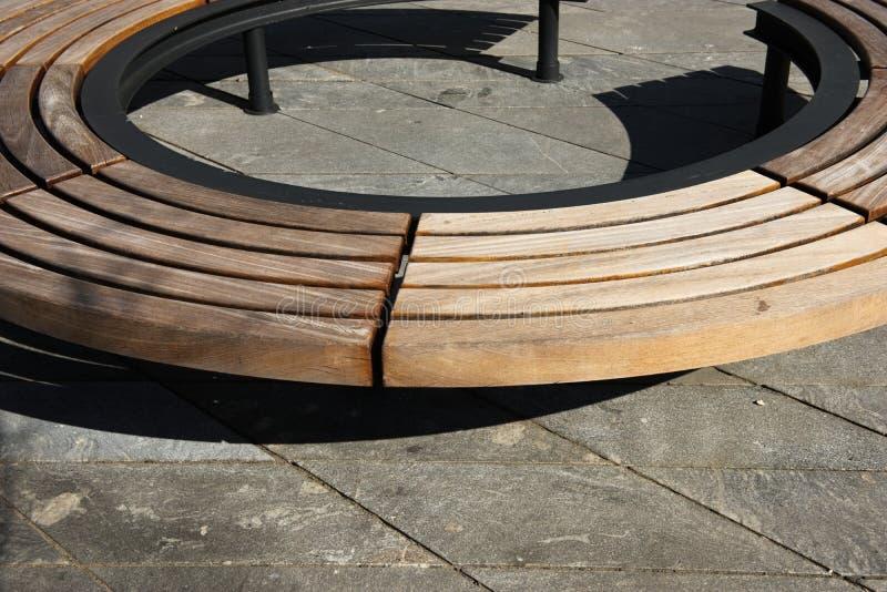 Diseño moderno de madera alrededor del banco de parque circular imagenes de archivo