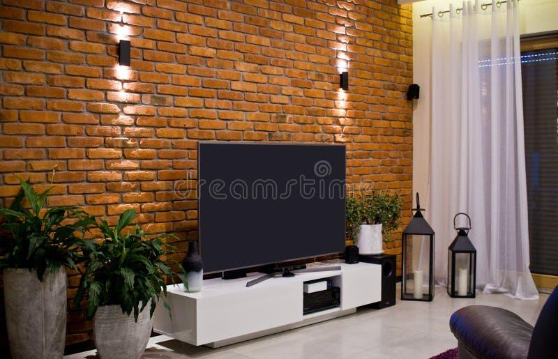 Diseño moderno del sitio casero con la pared de ladrillo roja y la televisión llevada plana fotos de archivo libres de regalías
