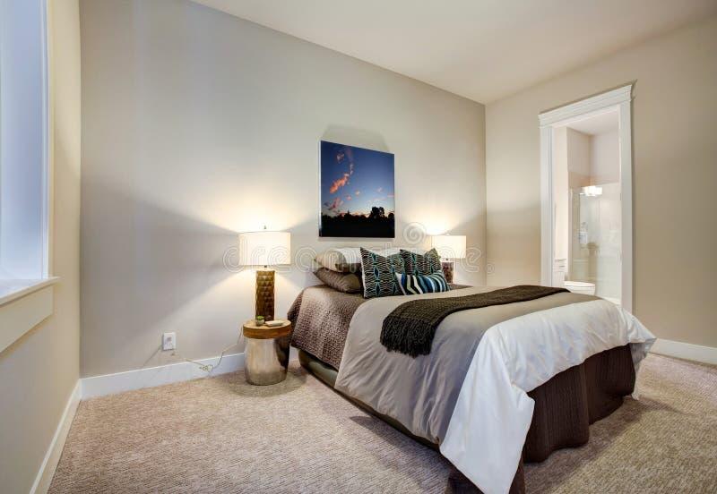 Diseño neutral del dormitorio con el cuarto de baño de la habitación del en fotografía de archivo