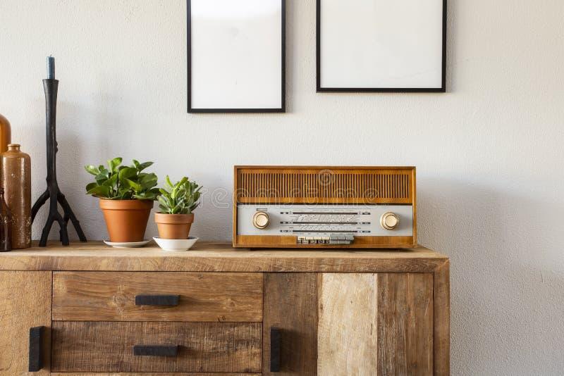 Diseño retro de la sala de estar con el gabinete y la radio junto con las plantas verdes y las pinturas en blanco, pared blanca imagen de archivo libre de regalías
