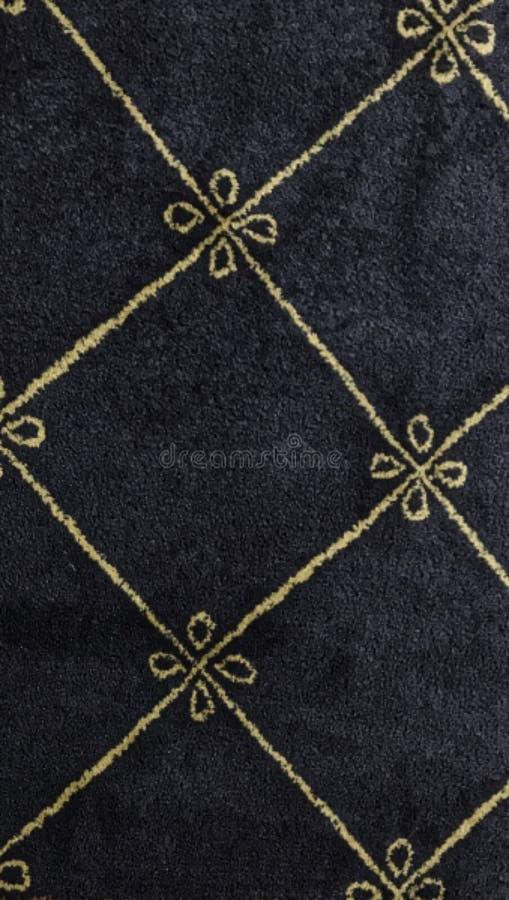 Diseño simple de la alfombra Fondo azul de la alfombra con las líneas del oro bordadas fotos de archivo