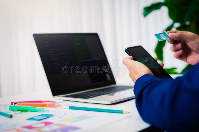 Diseño web de trabajo de la prueba del programador nuevo en el ordenador portátil del ordenador con el teléfono móvil en oficina  imágenes de archivo libres de regalías