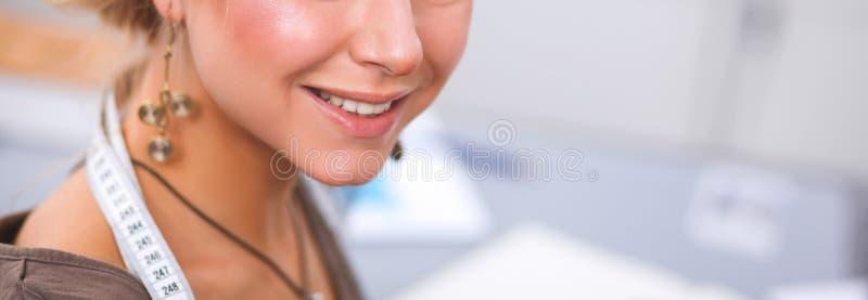 Dise?ador de moda de sexo femenino sonriente que se sienta en el escritorio de oficina foto de archivo
