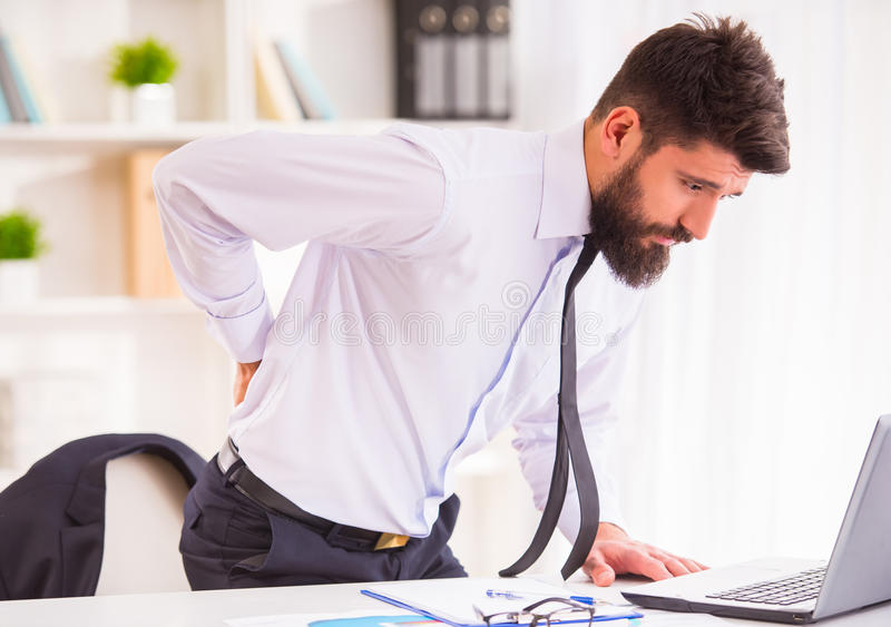 Disease in the office. Disease back. Portrait of a businessman with a beard while working in his office, holding behind his back royalty free stock image