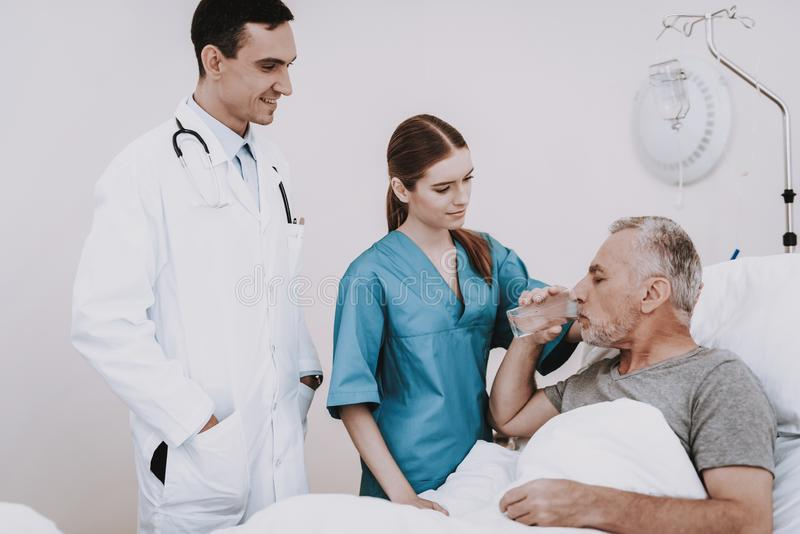 Nurse and Doctor Help Patient. Clinic and Old Man. royalty free stock photos