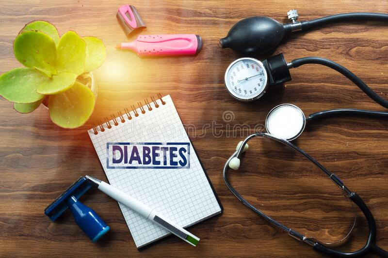 Disease stop diabetes concept text writing on white notebook and black stethoscope, sphygmomanometer on wood table. Disease stop diabetes concept text writing royalty free stock images