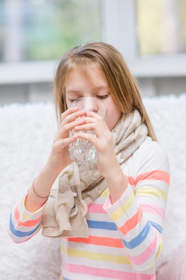 Diseased girl drinks water. Diseased little girl drinks water stock photos