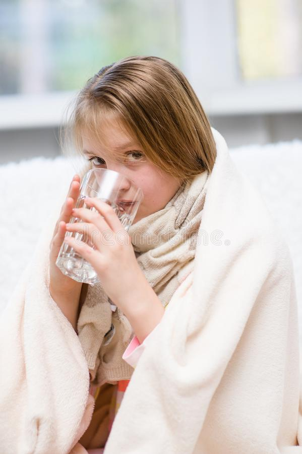 Diseased girl drinks water. At home stock image
