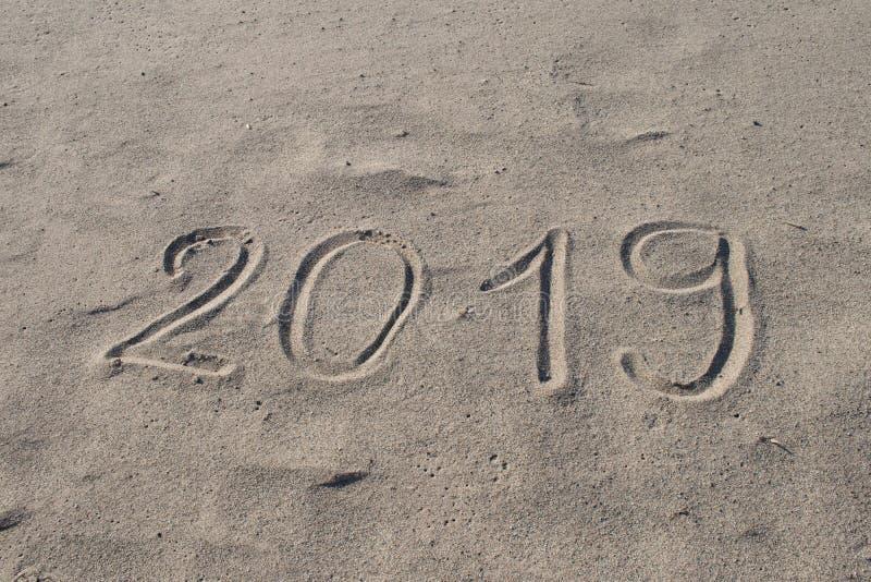 2019 disegnati a mano sulla sabbia Il nuovo anno sta venendo o le feste catalogano la progettazione astratta del fondo immagine stock