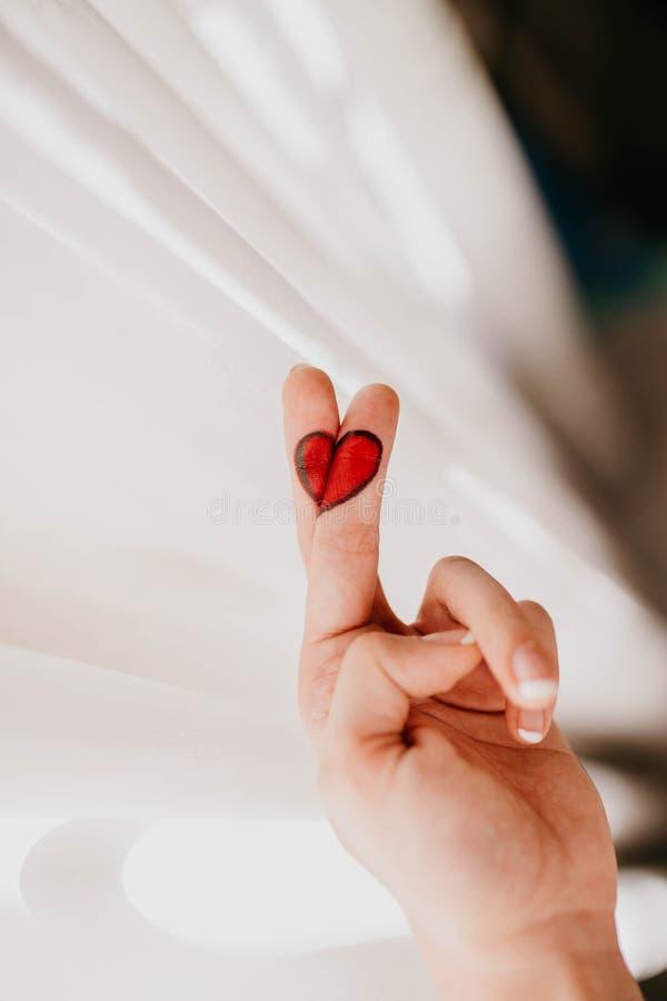 Disegno del cuore rotto nelle dita fotografia stock
