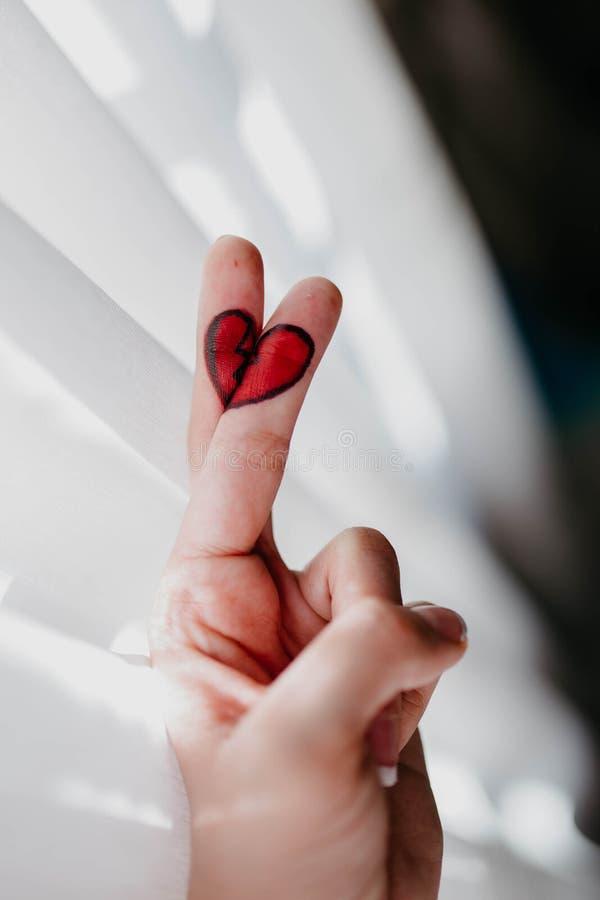 Disegno del cuore rotto nelle dita fotografia stock libera da diritti