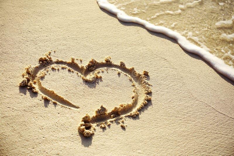 Disegno del cuore sulla sabbia della spiaggia fotografie stock libere da diritti