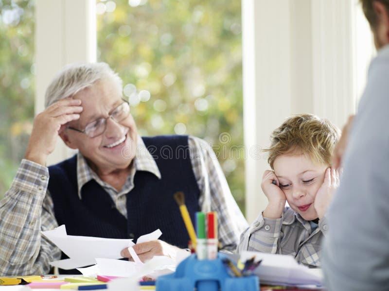 Disegno del ragazzo con i pastelli con il padre And Grandfather immagine stock libera da diritti