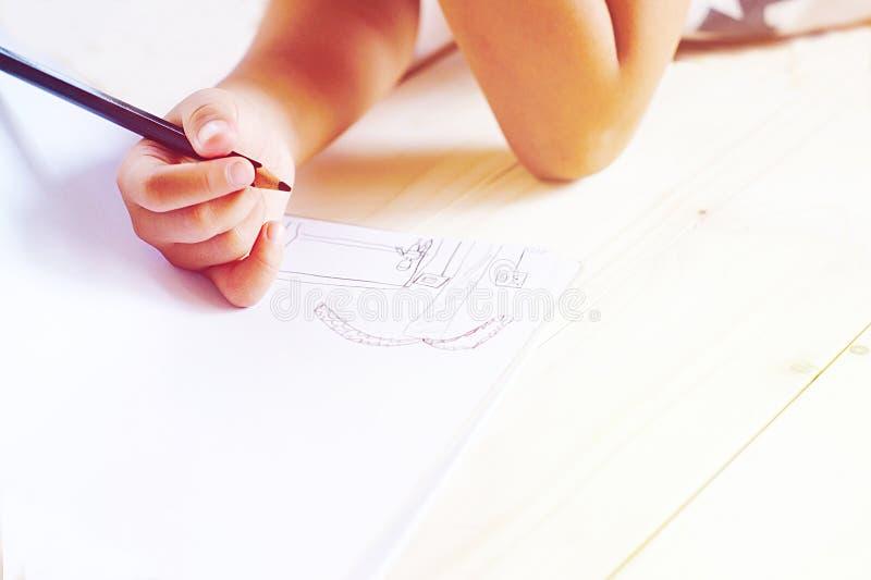 Disegno della mano del ` s del bambino qualcosa su Libro Bianco fotografia stock