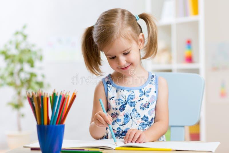 Disegno della ragazza del bambino con le matite variopinte in scuola materna immagini stock libere da diritti