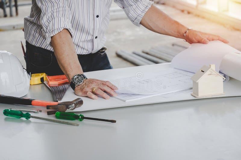 Disegno di architetti, ingegneri o interni con progetto e strumenti sulla tavola conferenze presso il centro uffici del cantiere fotografia stock libera da diritti