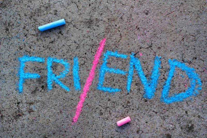 Disegno di gesso: conclusione di amicizia AMICO di parola diviso nella metà fotografie stock