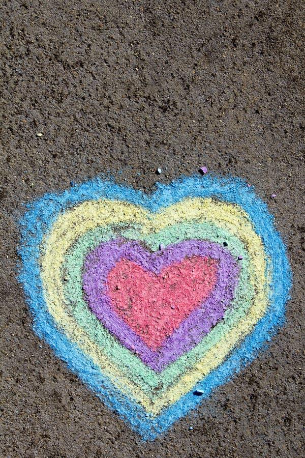Disegno di gesso: cuori variopinti su asfalto fotografia stock