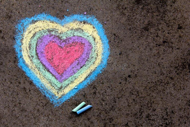 Disegno di gesso: cuori variopinti su asfalto fotografie stock