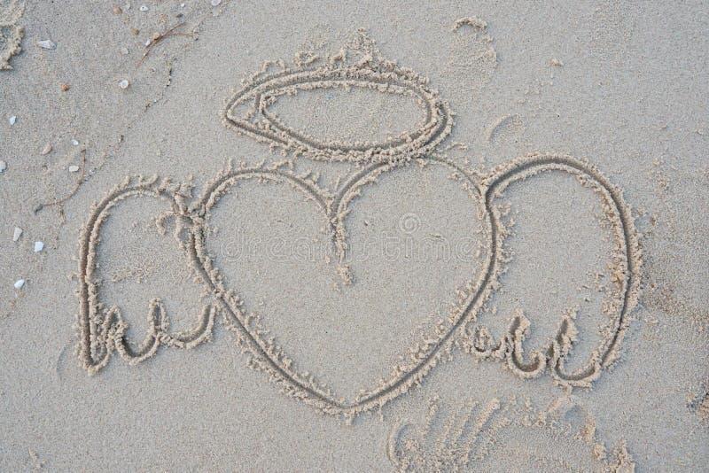 Disegno di un cuore su una spiaggia di sabbia immagine stock