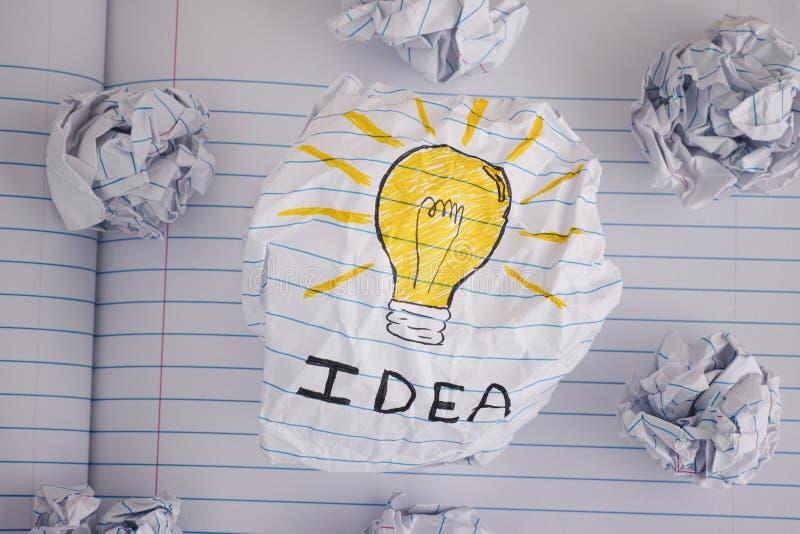 Disegno di una lampadina con l'idea di parola sulla palla di carta sgualcita immagine stock libera da diritti