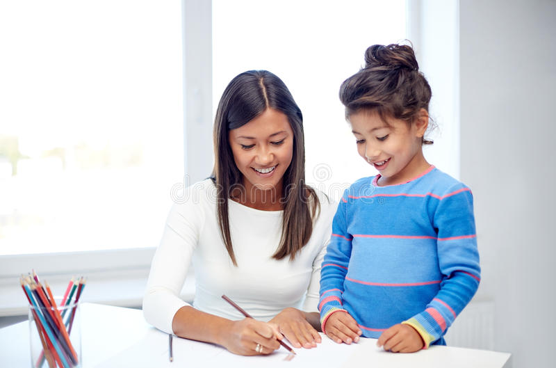 Disegno felice della figlia e della madre con le matite fotografia stock