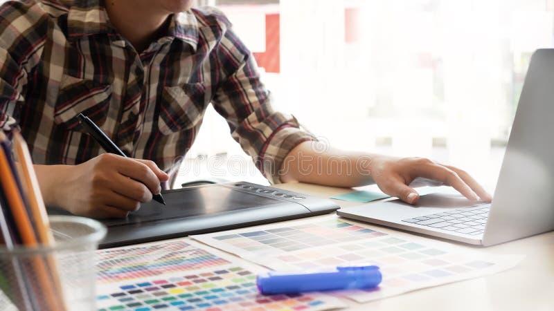 Disegno grafico sulla tavoletta digitale con penna, designer grafico che lavora sul workspace creativo fotografia stock libera da diritti