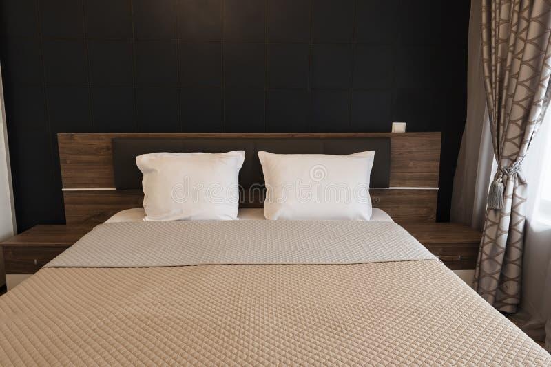 Disegno interno della camera da letto moderna Grande letto, stanza con il tono marrone di colore Windows con le tende e le tosatu fotografia stock libera da diritti