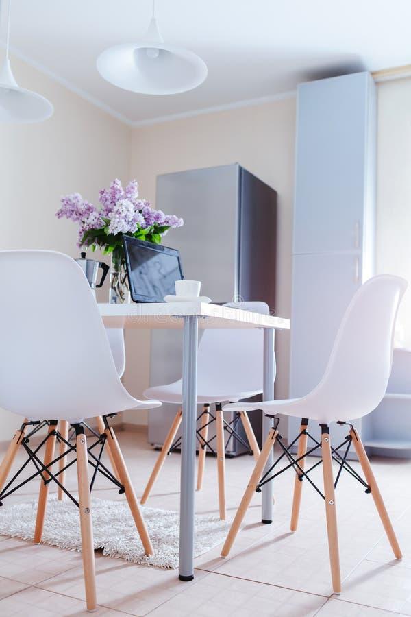 Disegno moderno della cucina Interno di sala da pranzo leggera decorato con i fiori lilla Computer portatile e caffè sulla tavola fotografie stock