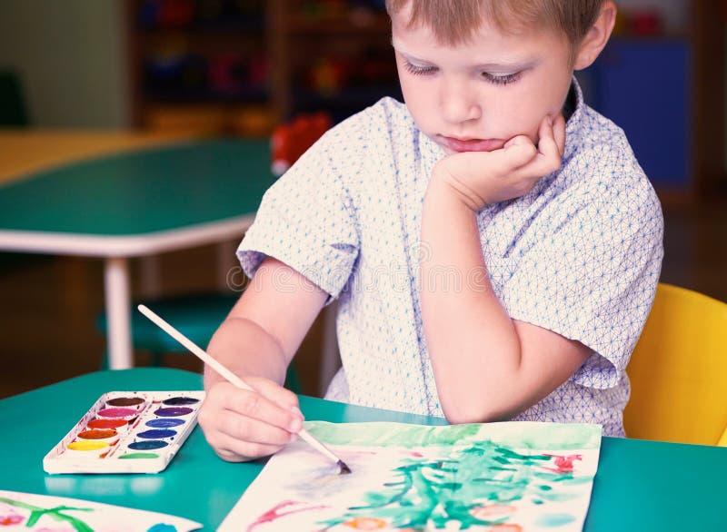Disegno sveglio del ragazzo di Llittle con gli acquerelli variopinti Scuola, concetto di istruzione fotografia stock