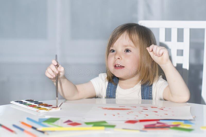 Disegno sveglio della bambina con la pittura a casa fotografie stock