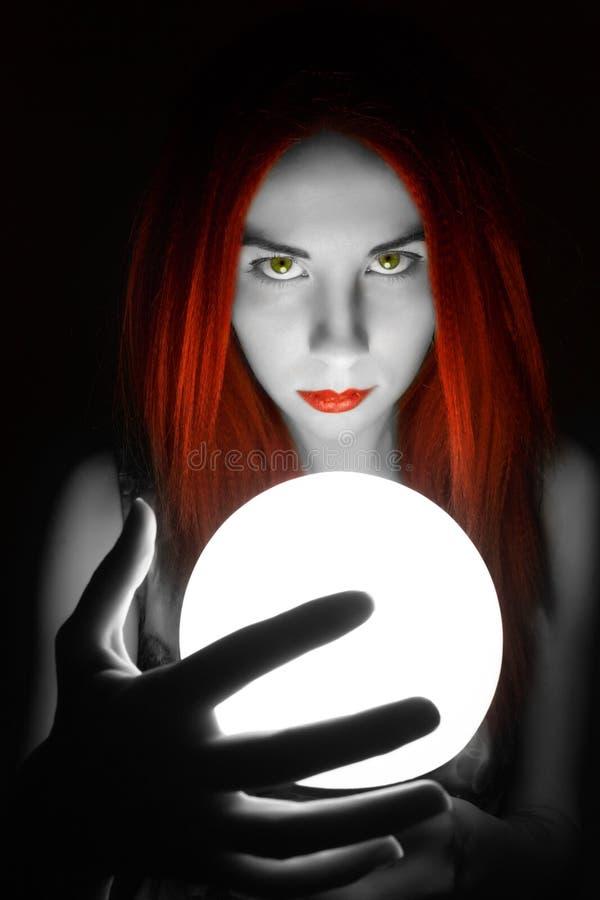 Diseur de bonne aventure roux magnifique tenant la boule de cristal la belle femme essaye d'examiner l'avenir photo stock