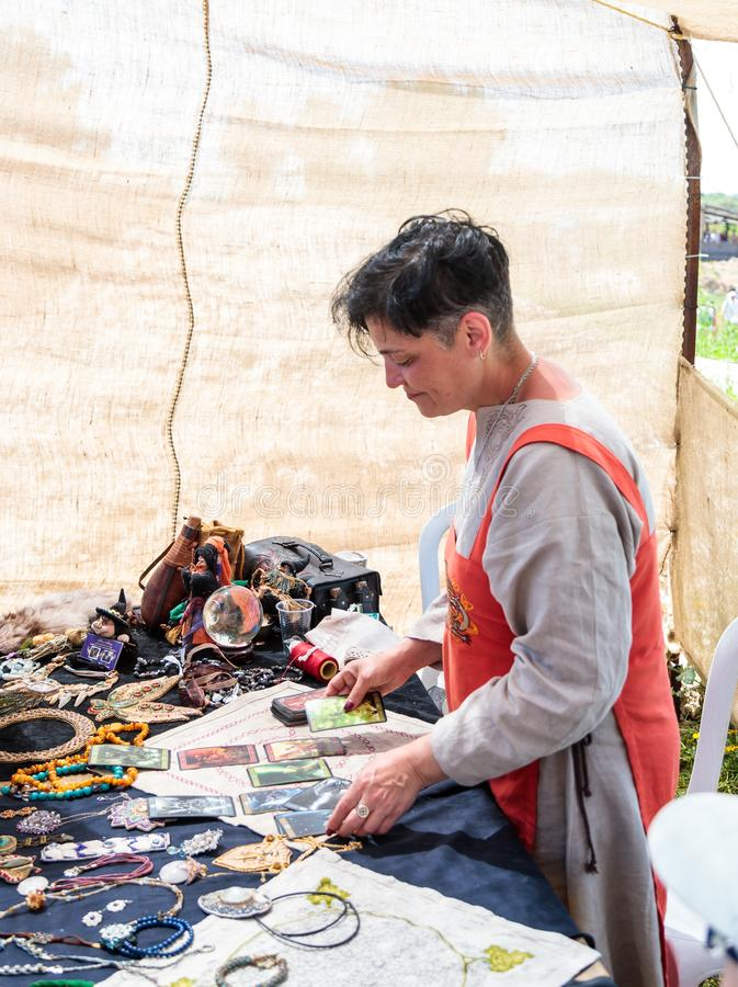 Diseur de bonne aventure sur des cartes de tarot - le participant du festival de chevalier place des cartes dans le parc de Goren photos stock