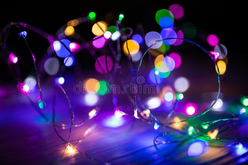 Disfocused blurred Christmas bokeh lights over dark background stock photography