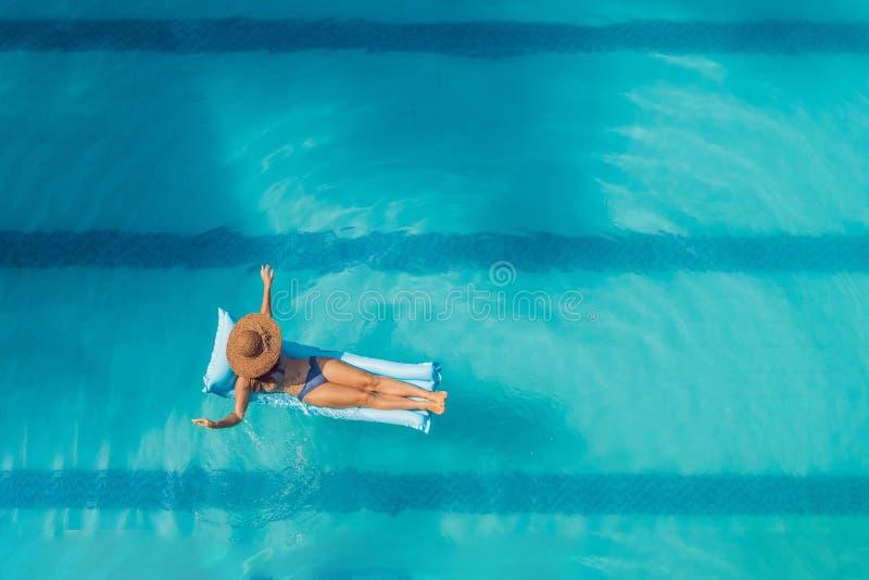 Disfrutar de bronceado Concepto de las vacaciones Opinión superior la mujer joven delgada en bikini en el colchón de aire azul en fotografía de archivo