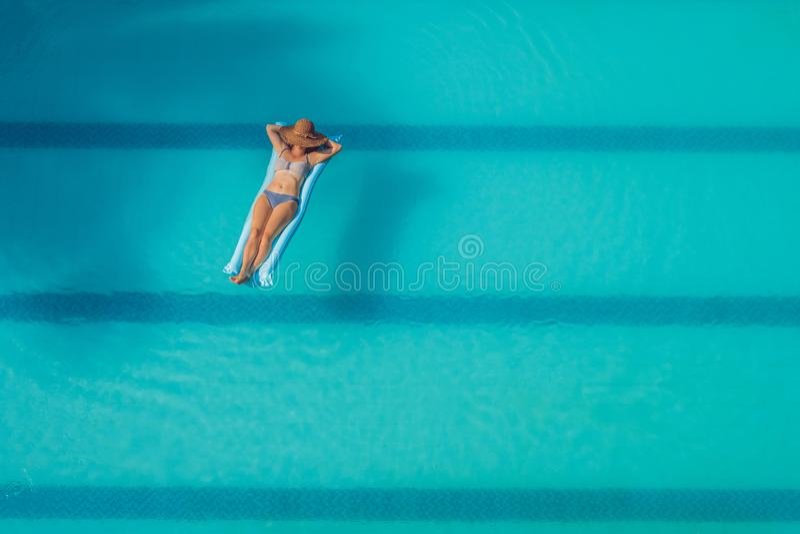 Disfrutar de bronceado Concepto de las vacaciones Opinión superior la mujer joven delgada en bikini en el colchón de aire azul en imagenes de archivo