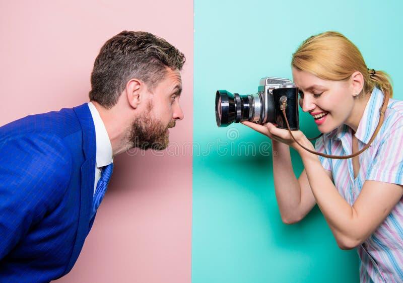 Disfrutar de la sesión de la sesión fotográfica Modelo masculino que tira del fotógrafo en estudio Mujer bonita que usa la cámara foto de archivo libre de regalías