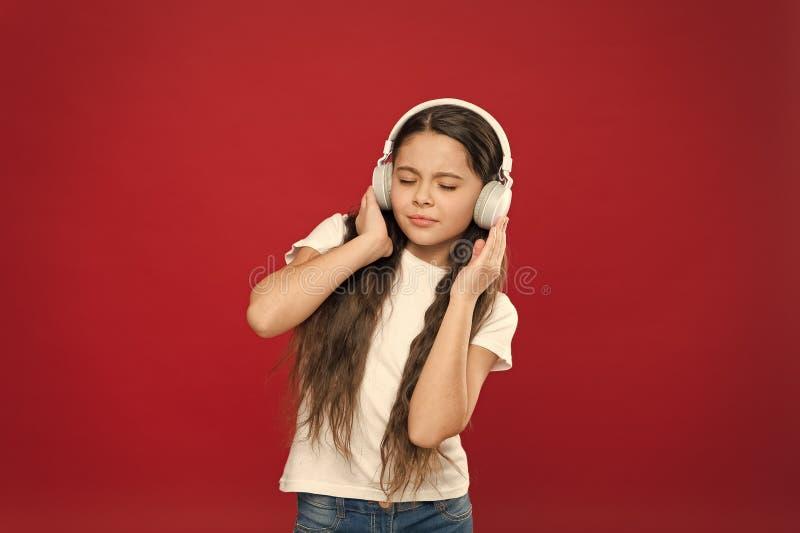 Disfrutar de su m?sica preferida Peque?a muchacha que lleva los auriculares est?reos Ni?a que escucha la m?sica Fan de m?sica lin foto de archivo libre de regalías