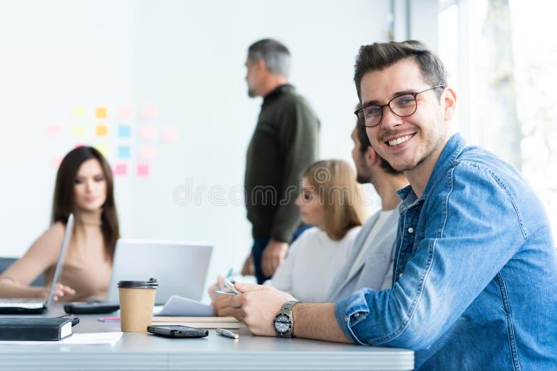 Disfrutar de su trabajo Hombre joven hermoso que mira la cámara y que sonríe mientras que sus colegas que trabajan en el fondo fotografía de archivo libre de regalías
